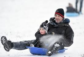 a child tobogganing with his father