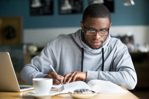 Young African-American male with glasses taking notes and studying in coffee shop