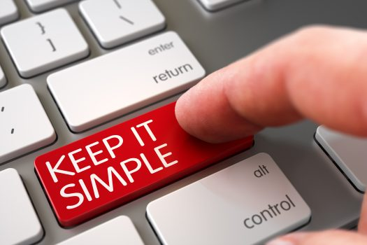 """Caucasian finger pressing down on keyboard button that says """"keep it simple"""" and is highlighted in red."""