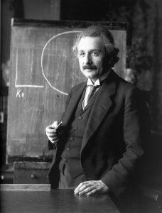 black and white picture of Einstein in front of blackboard