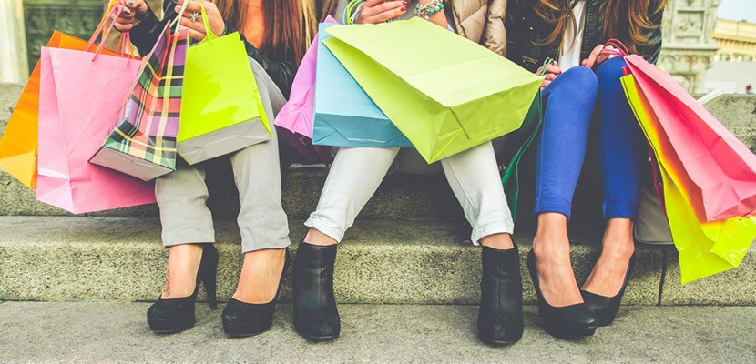 a few girls holding multiple shopping bags