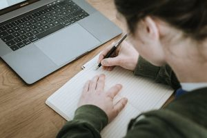a photo of a student writing in a notebook.