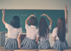 girls sitting in front of the chalkboard