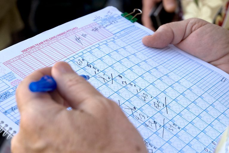 A coach filling out a baseball stat sheet