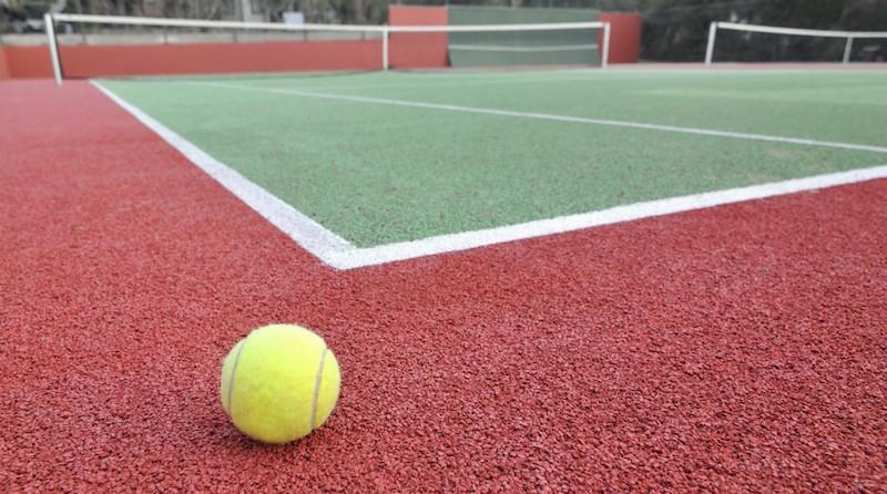 A tennis ball by a court