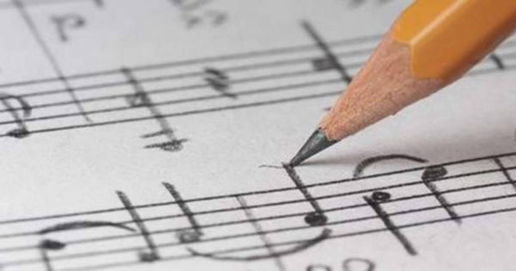A person writing on a music score.