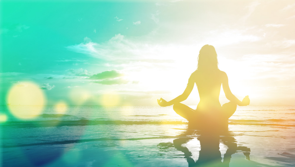 A woman meditating in front of the ocean.