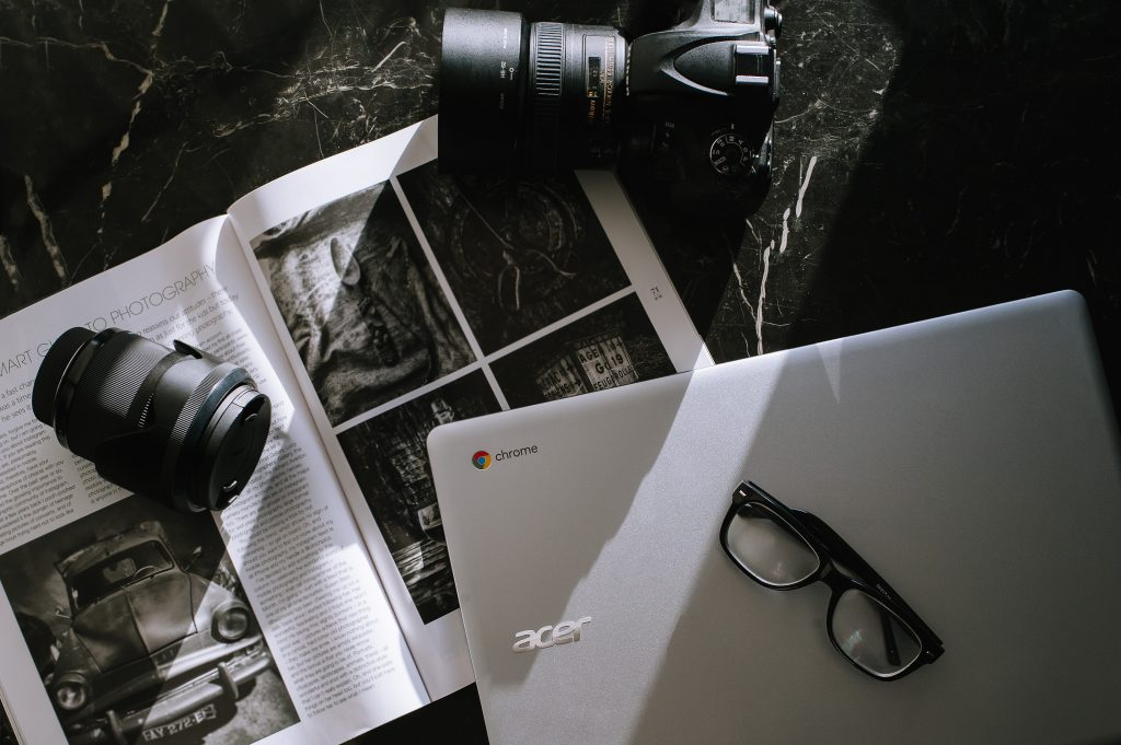 Photography spread with a magazine, camera, laptop and glasses, via Anete Lusina on Unsplash