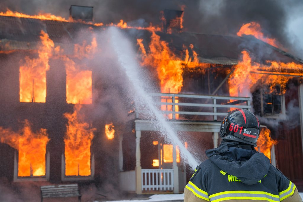 Firefighter putting out flames outside of a burning building with a hose, via Daniel Tausis on Unsplash