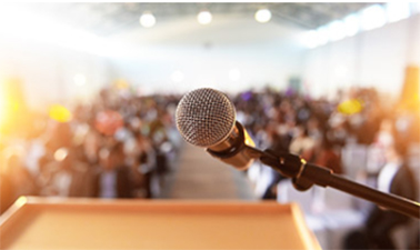 A microphone and podium in front of a crowd