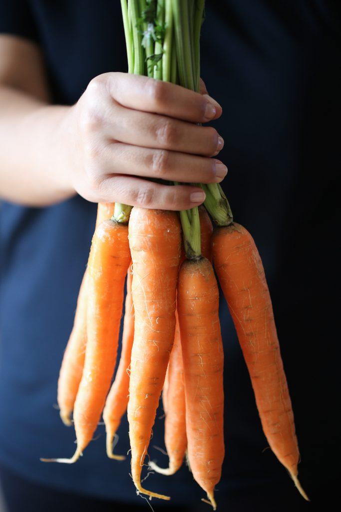 Women holds multiple fresh carrots, via Rebecka Sendroiu on Unsplash