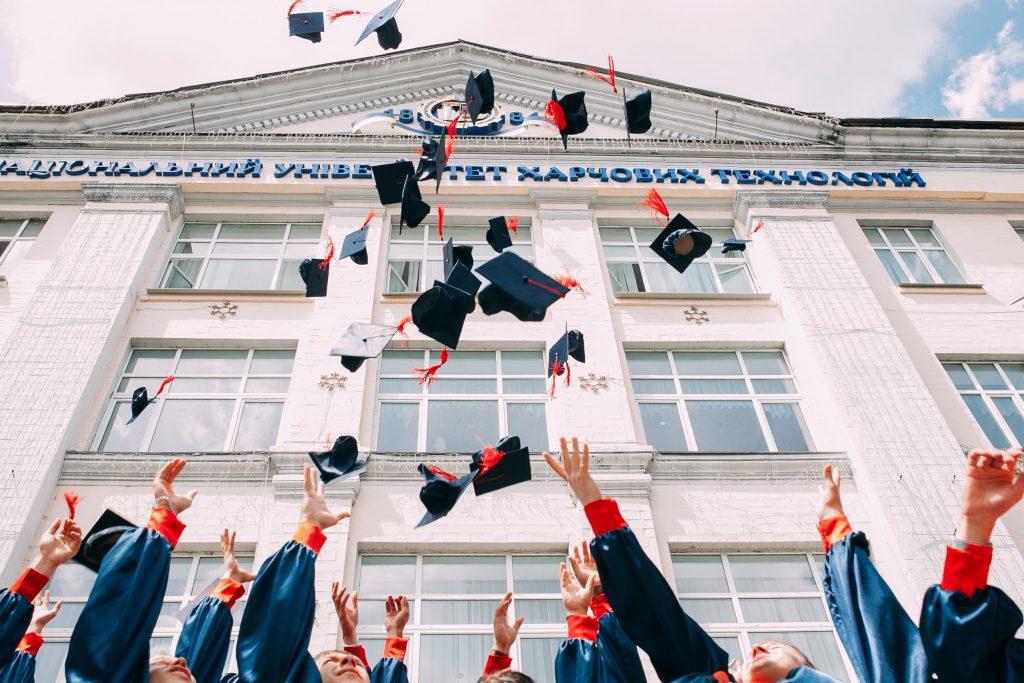 College students throw caps into the air at graduation, via Vasily Koloda on Unsplash