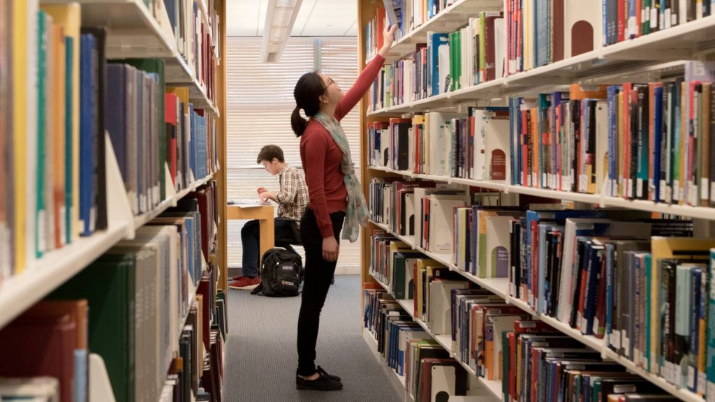 student in library reaching for a book on financial discount rates