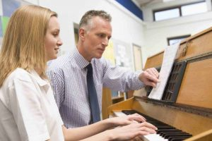 A teenager learning piano with her professor
