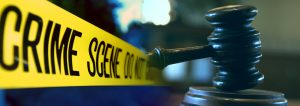 Photo of a yellow tape from a crime scene and a gavel