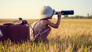 A kid searching in the field with binoculars.