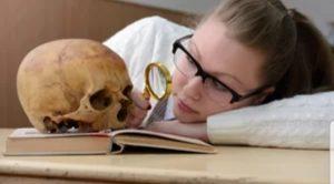 A woman looking at a human skull.