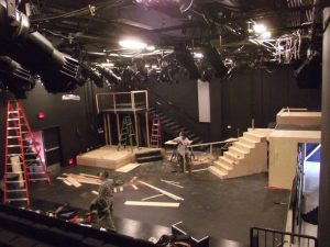 The backstage of a theater with sets being built.