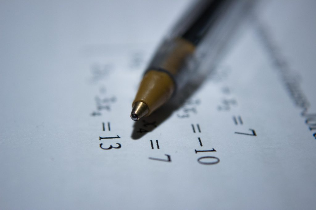 a pen in focus over math equations.