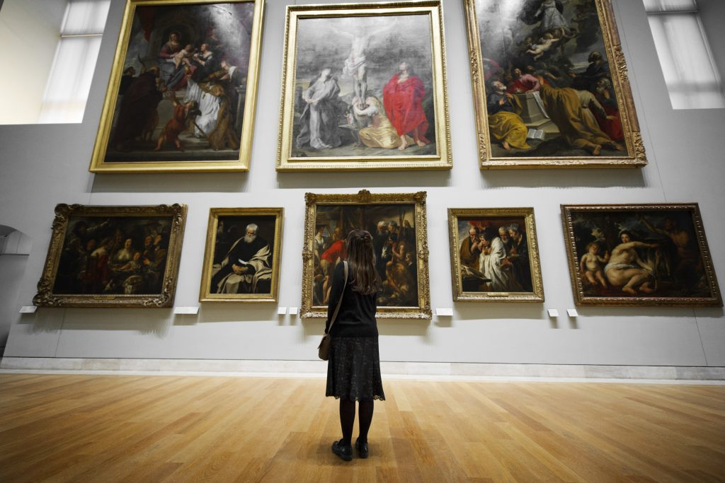 A picture of a woman looking at framed art.