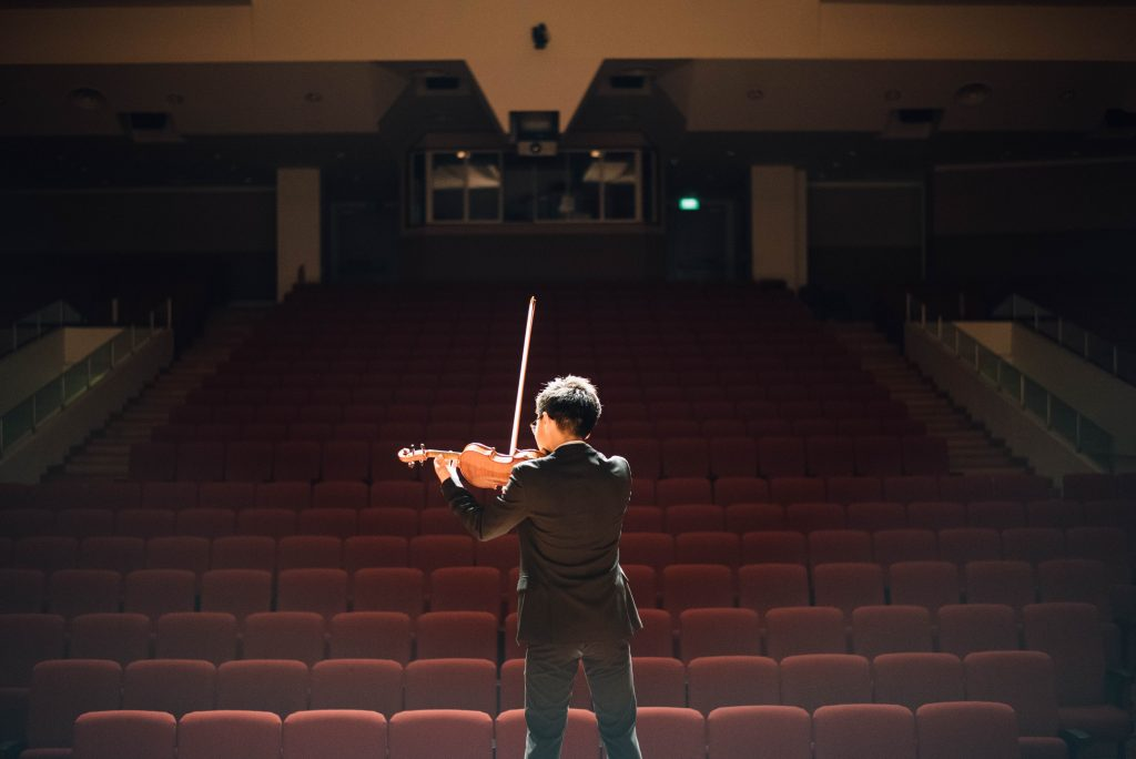 a man plays the violin on stage before an empty auditorium.