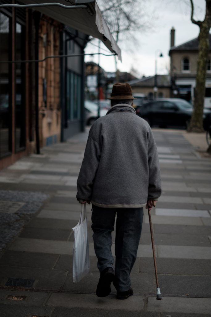 an older man with a can and white shopping bag walks along a sidewalk.