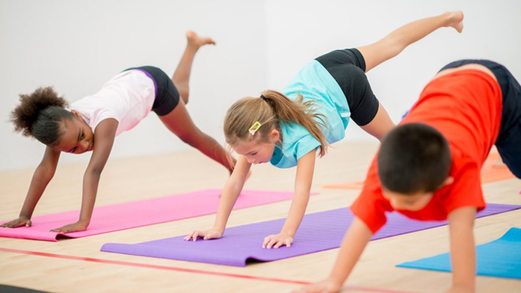 An image of kids practicing yoga poses.