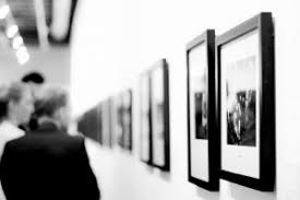 Black and white photo of people appreciating art in a gallery