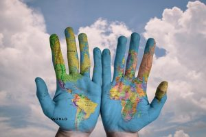 a picture of hands with the world on them