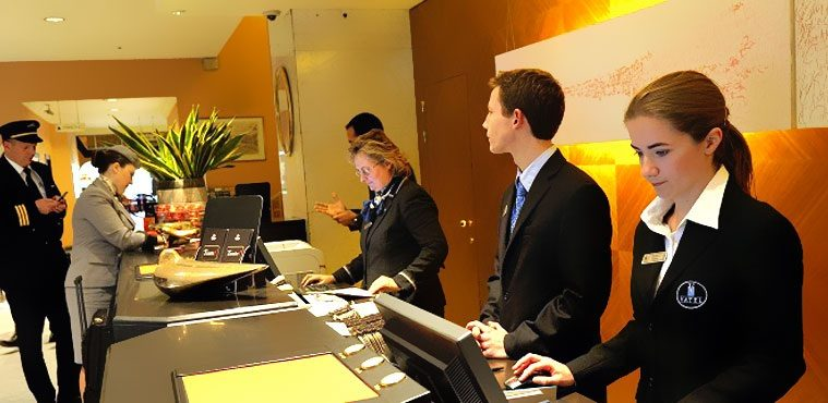 This is an image of young professionals manning the counter of a hospitality industry.