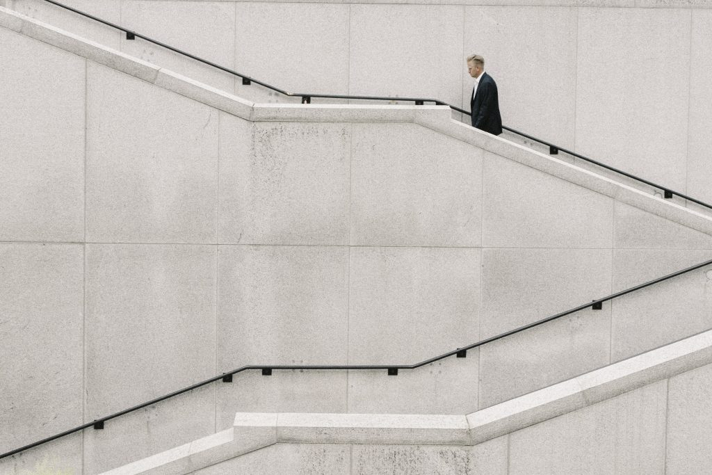 a man in a suit walks up a flight of stairs.