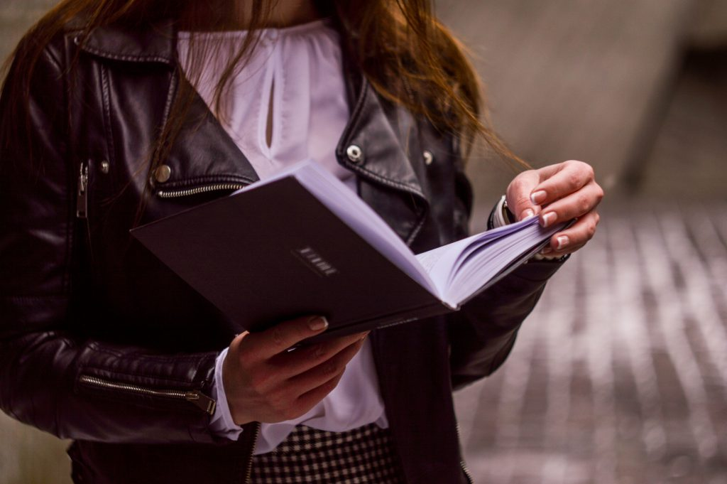 a woman in a leather jacket reads a book.