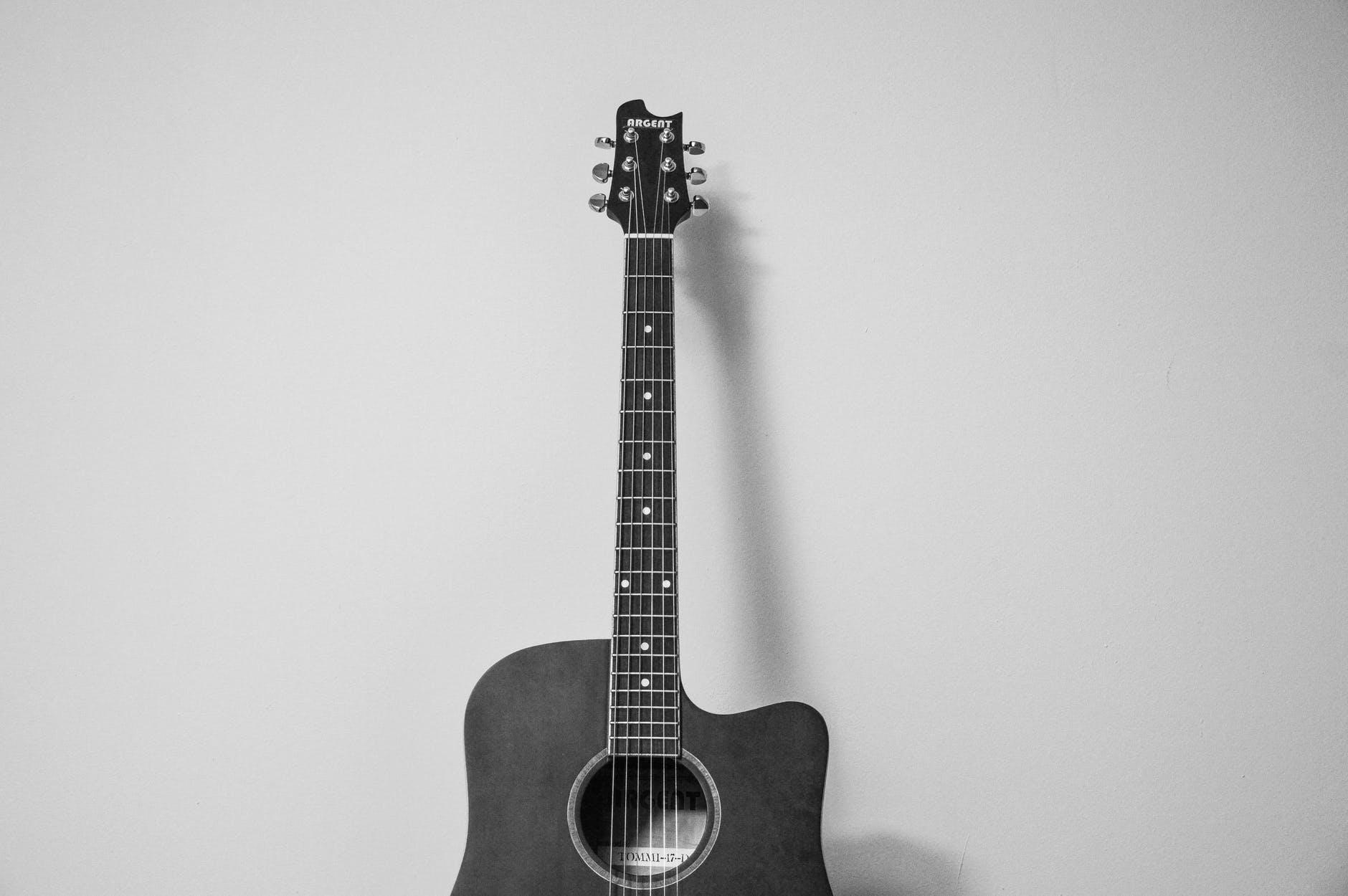 A guitar lying against a blank wall