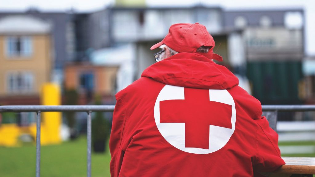 picture of person wearing red cross symbol on jacket