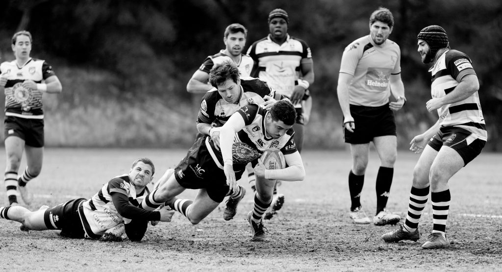 rugby platers in white jerseys tackle one another on a field.