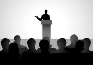 A person speaking in front of an audience