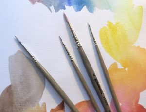 Picture of paintbrushes lying on top of a paper with watercolor paint on it