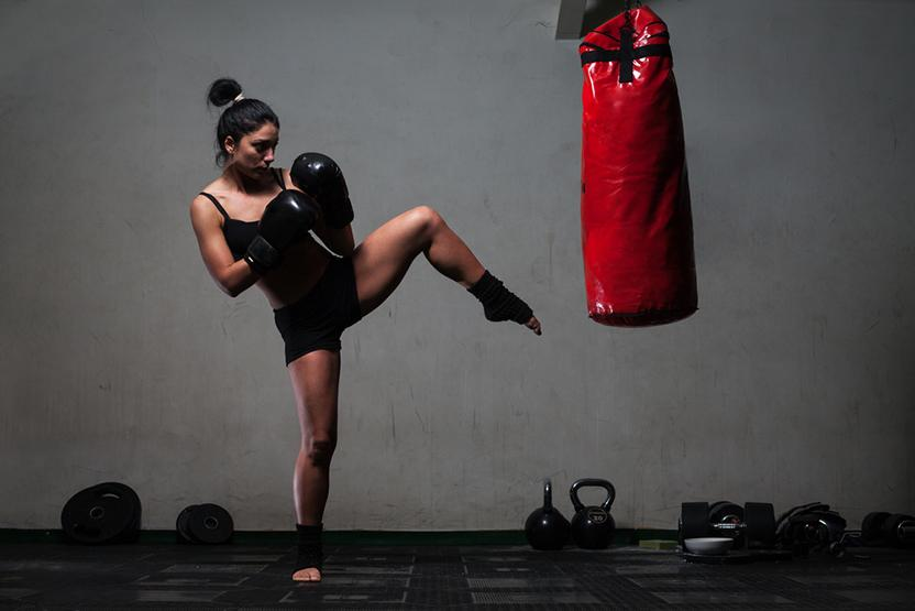 A woman kicking a kickboxing bag.