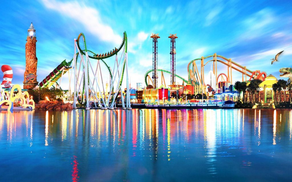 view of an amusement park from the water showing rides and other attractions.