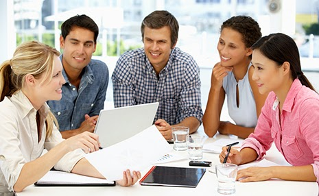Stock Photos of Employees Gathered Around a Report