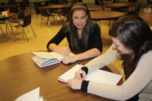 An image of Elms College students writing together
