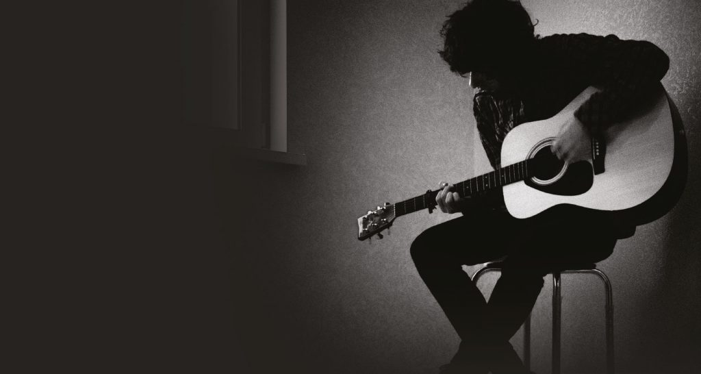 A man playing an acoustic guitar.