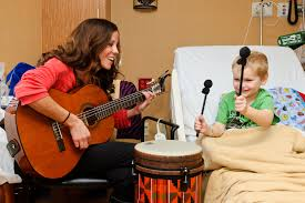 This image is of a music therapist helping a child in need of healing.
