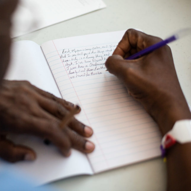 A man writing in a journal.