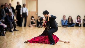 Two ballroom dancers performing in a room.