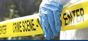 Picture of a gloved hand holding crime scene tape