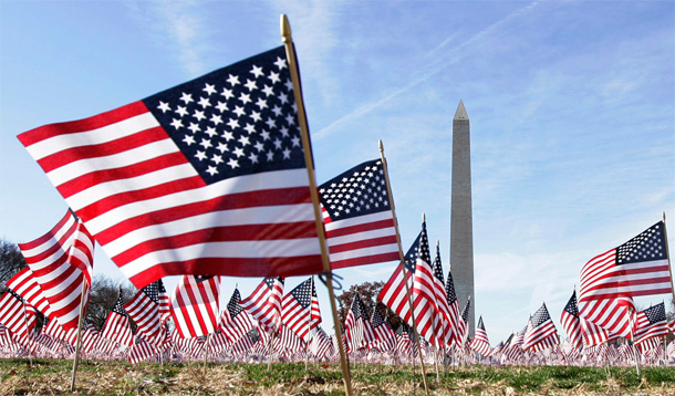 A mob of American flags in front of the Washington monument.