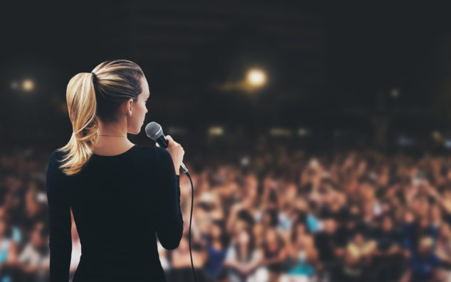 A woman delivering a speech to a group of audience.