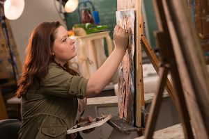 An image of a Studio Arts major at CNR painting at her easel