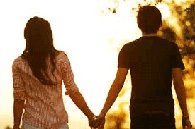 Boy and girl holding hands walking in the sunset